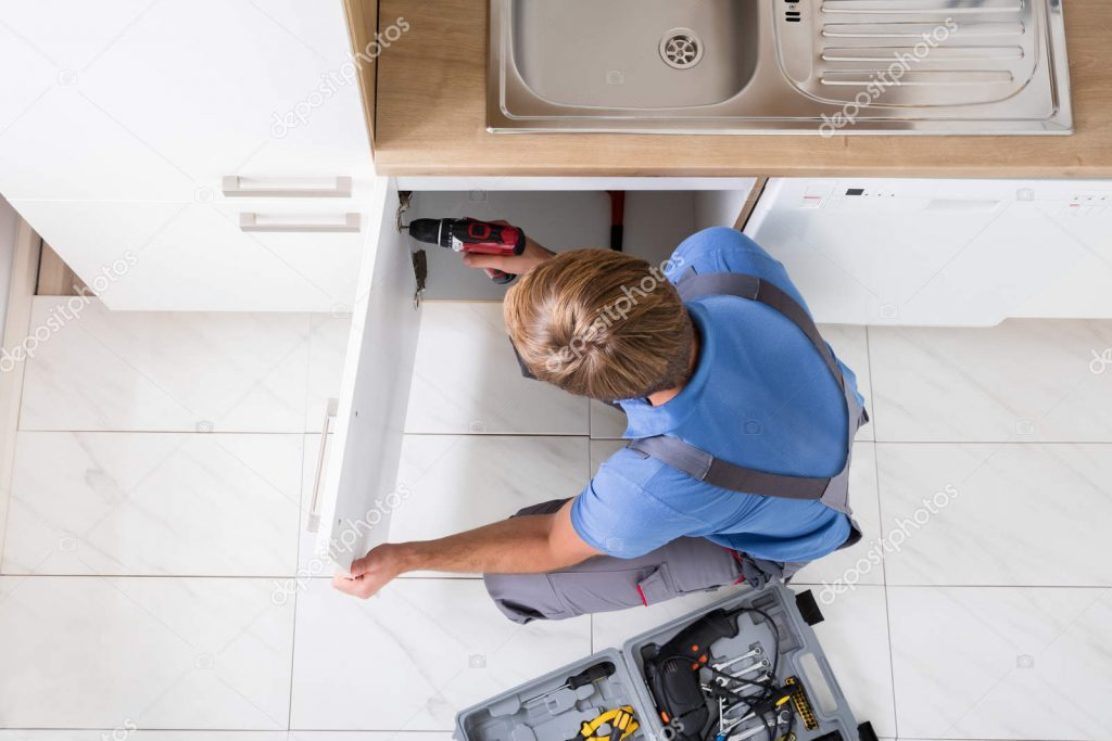 depositphotos 142431395 stock photo man repairing cabinet